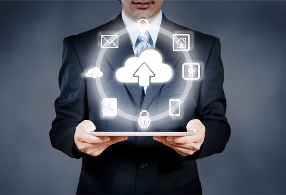 Business man holding a tablet with several icons floating above it in a circular pattern