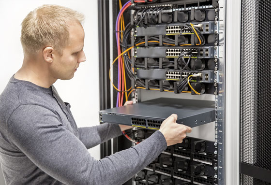 Man installing a server in a rack system